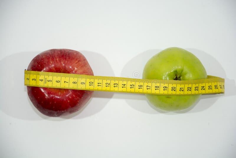 mele rosse e verdi, con nastro adesivo di misurazione fotografia stock libera da diritti
