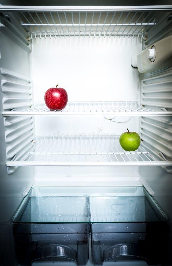 Mele rosse e verdi fresche luminose sullo scaffale del frigorifero vuoto aperto Concetto di dieta di perdita di peso fotografia stock