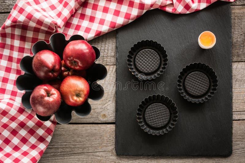 Mele rosse mature sul bordo di legno con l'asciugamano a quadretti rosso intorno e gli accessori per cuocere immagini stock libere da diritti