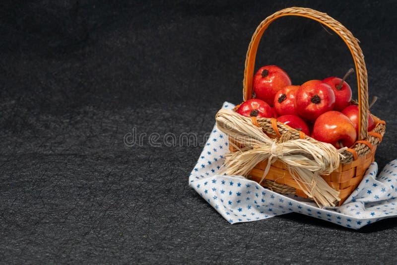 Mele rosse mature in un canestro della paglia con un tovagliolo del motivo a stelle Bl immagine stock libera da diritti