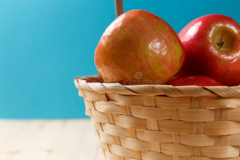Mele rosse mature in un canestro su un di legno luminoso fotografia stock libera da diritti