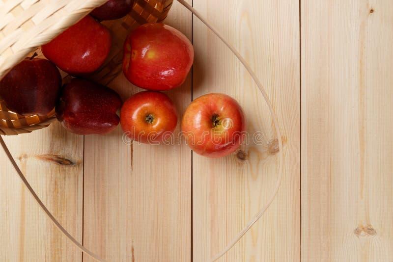 Mele rosse mature in un canestro su un fondo di legno luminoso immagini stock libere da diritti