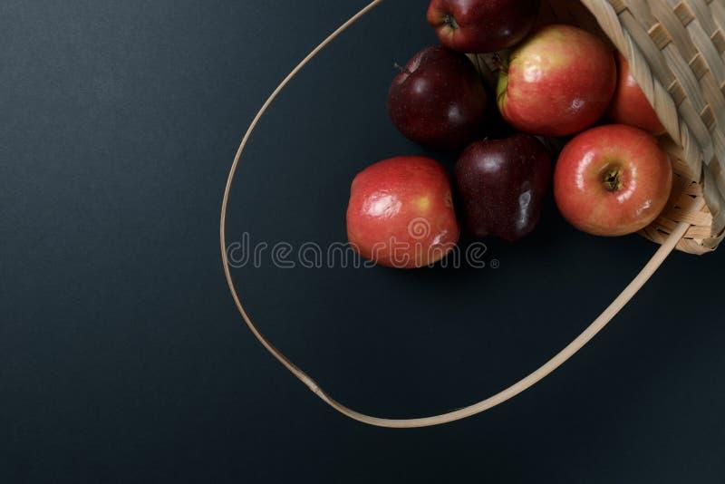 Mele rosse mature in un canestro su un fondo scuro fotografia stock