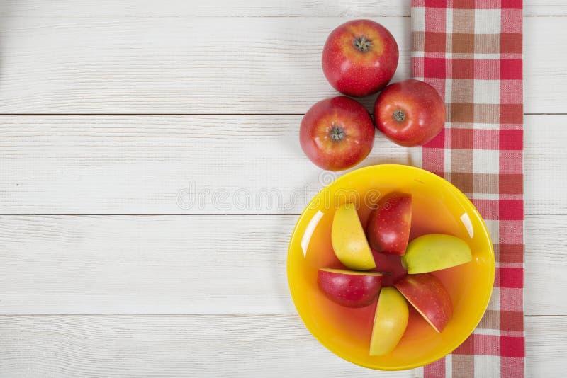 Mele su superficie di legno con la tovaglia a quadretti della cucina nella vista superiore fotografie stock libere da diritti