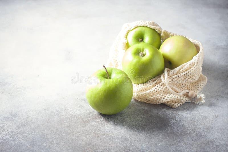 Mele verdi organiche nella borsa di rete riutilizzabile del cotone sulla tavola di legno Eco-pacchetto, concetto residuo zero fotografia stock libera da diritti