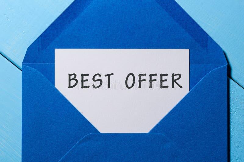 A melhor inscrição da oferta na letra no envelope azul Conceito da venda - mão com lupa imagens de stock royalty free