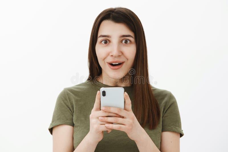 Melhor telefone tão fresco nunca Retrato da morena sem-palavras feliz impressa e fascinada no smartphone da terra arrendada 20s e foto de stock