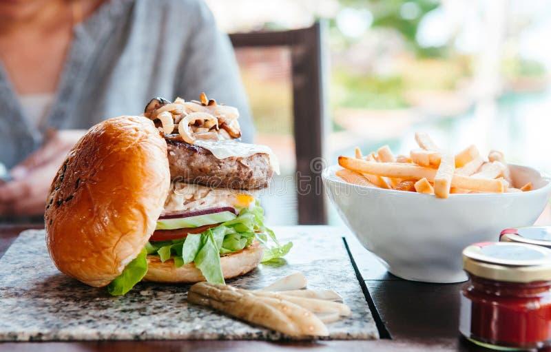 Melhore o hamburguer com queijo grelhado da cebola, clos fritados francês da alface foto de stock