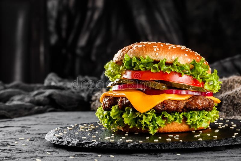 Melhore o hamburguer com queijo, tomates, as cebolas vermelhas, o pepino e a alface na ardósia preta sobre o fundo escuro Aliment fotos de stock