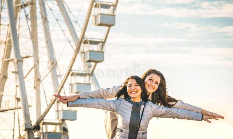 Melhores amigos das jovens mulheres que apreciam o tempo junto fora na roda da balsa imagem de stock