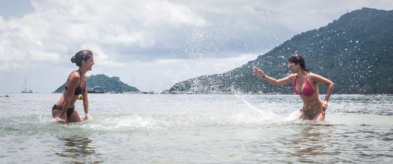 Melhores amigos no biquini que espirra a água, tendo o divertimento em férias fotos de stock royalty free