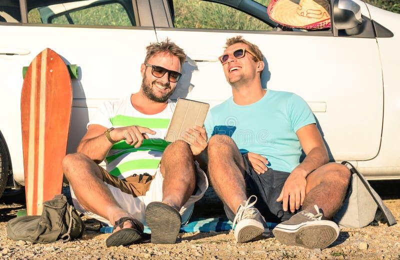 Melhores amigos novos do moderno que têm o divertimento com a tabuleta na viagem do carro imagens de stock royalty free