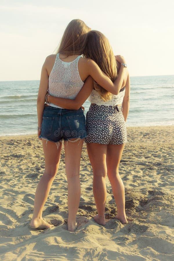 Melhores amigos que abraçam na frente do oceano no por do sol fotos de stock royalty free