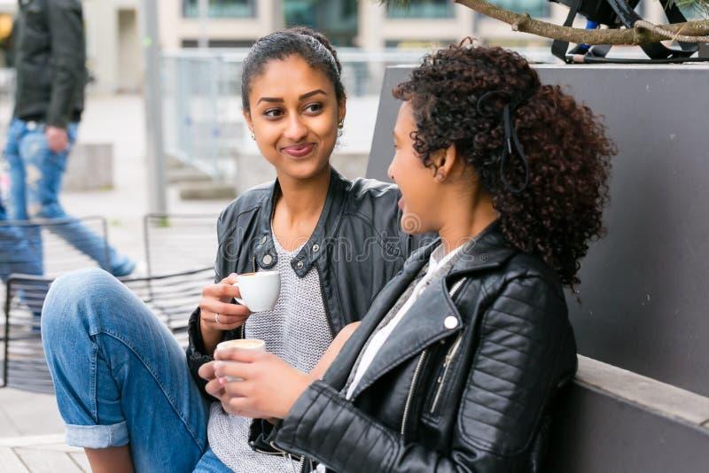 Melhores amigos que bebem o café na cidade imagens de stock royalty free