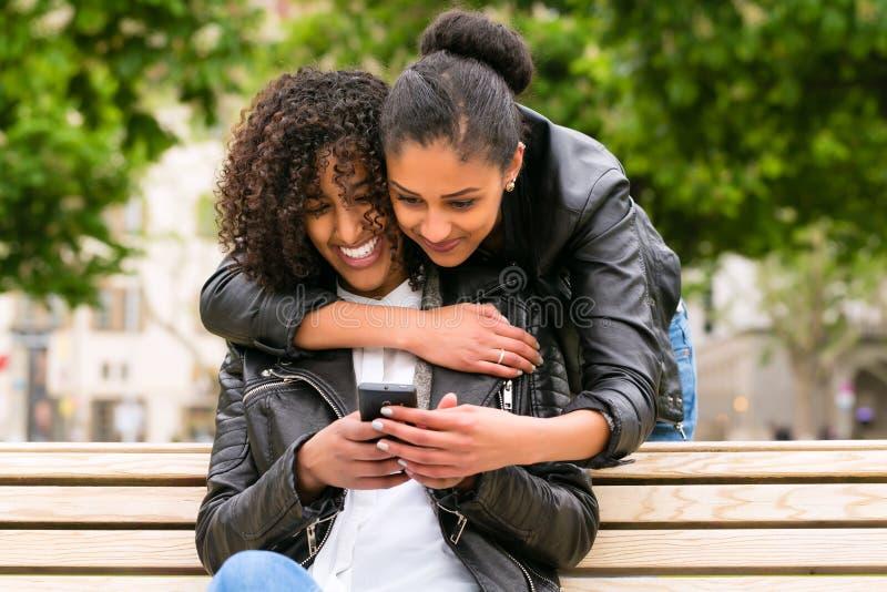 Melhores amigos que conversam com o smartphone no banco de parque fotos de stock royalty free