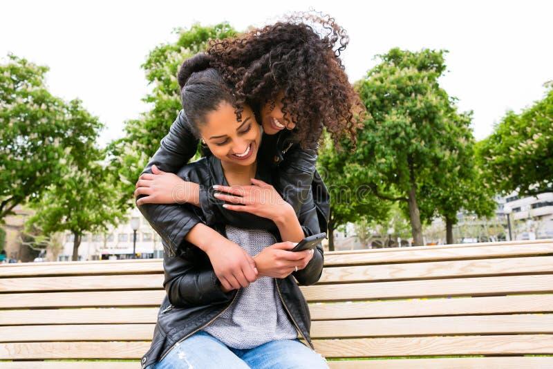 Melhores amigos que conversam com o smartphone no banco de parque foto de stock