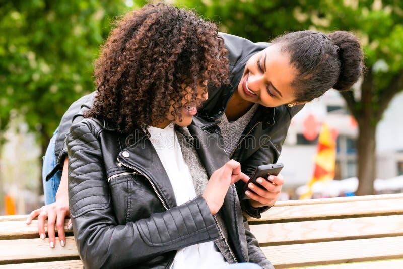 Melhores amigos que conversam com o smartphone no banco de parque imagem de stock