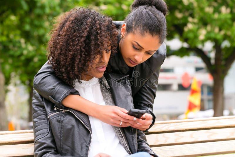 Melhores amigos que conversam com o smartphone no banco de parque foto de stock royalty free