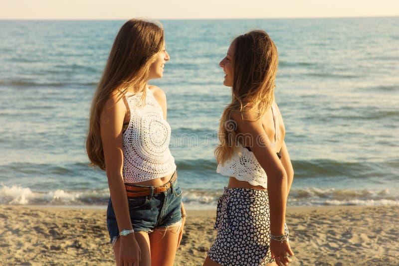 Melhores amigos que riem na frente do oceano no por do sol imagens de stock royalty free