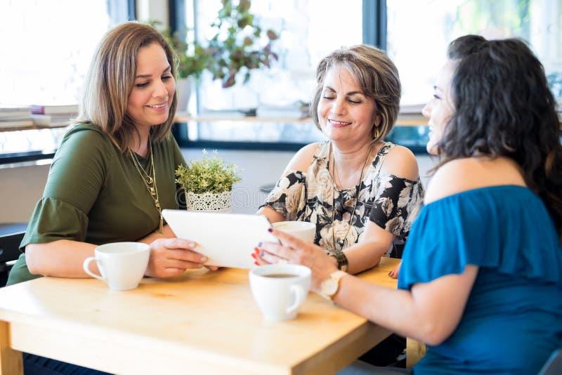 Melhores amigos que usam um tablet pc no café fotos de stock royalty free