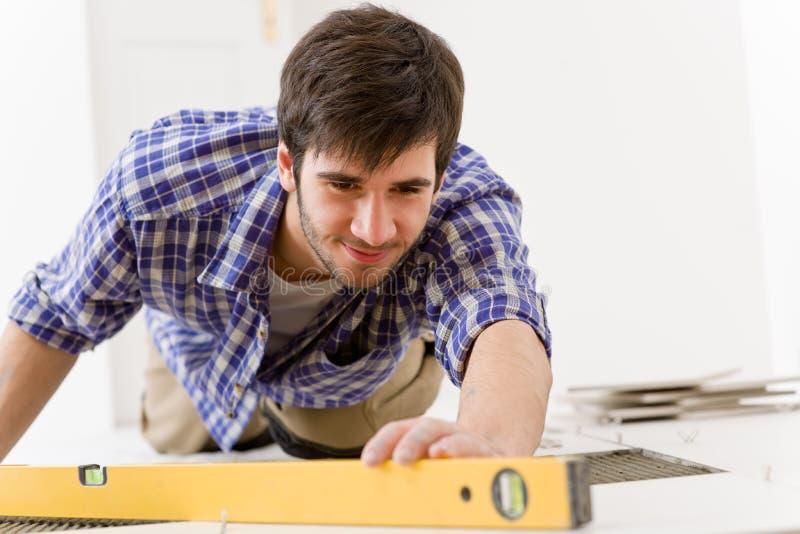 Melhoria Home da telha - trabalhador manual com nível foto de stock