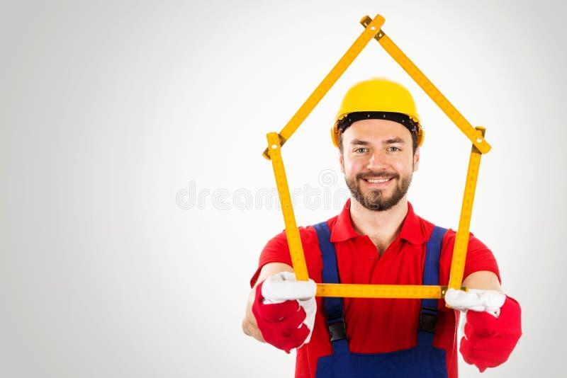 Melhoria home - o trabalhador manual com casa deu forma à régua nas mãos sobre foto de stock royalty free