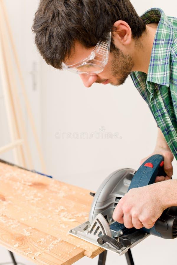 Melhoria Home - o trabalhador manual cortou a madeira com serra de vaivém imagens de stock royalty free