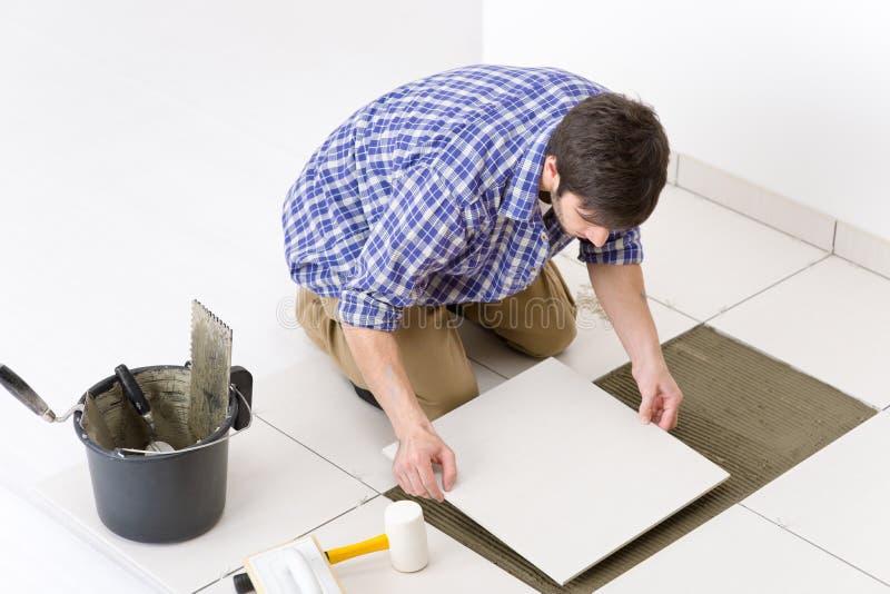 Melhoria Home - trabalhador manual que coloca a telha foto de stock