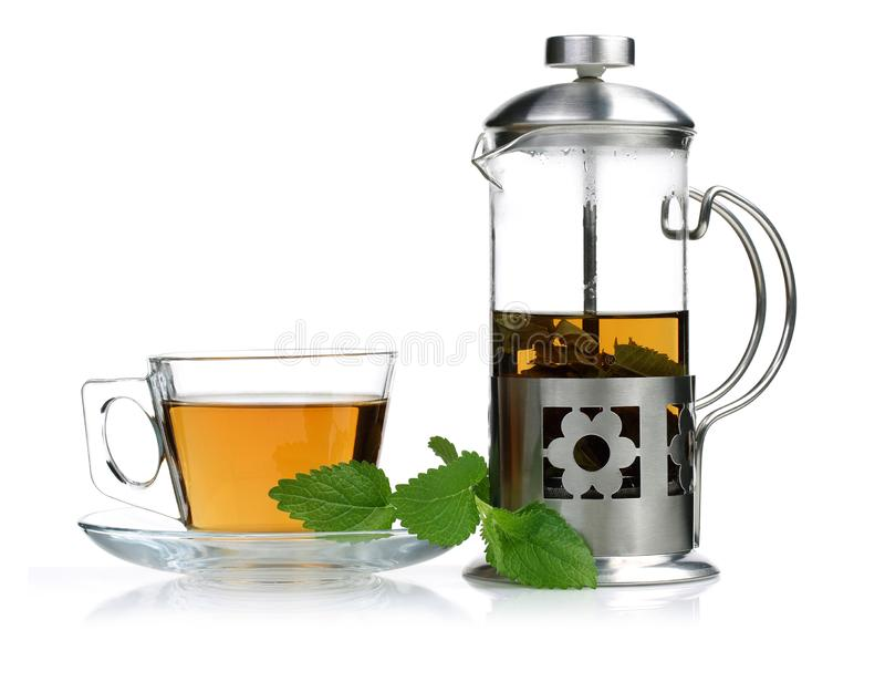 Melissa tea in a glass cup with lemon balm and teapot. Melissa tea in a glass cup with lemon balm leaves and teapot stock photo