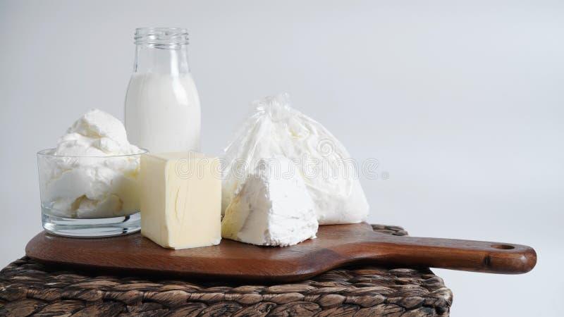 Melk, boter, kaas, zure room, kwarktribune op een houten raad stock foto