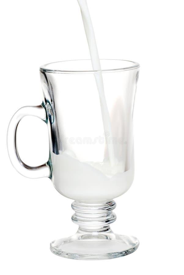 Melk die in de Mok van het Glas wordt gegoten stock foto's