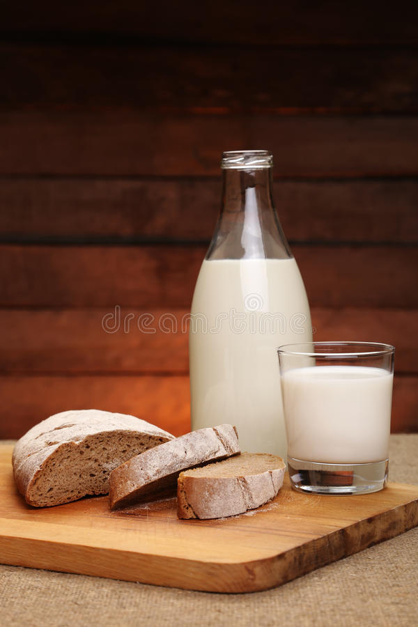 Melk en brood Melk in een van de glasfles en rogge brood royalty-vrije stock fotografie