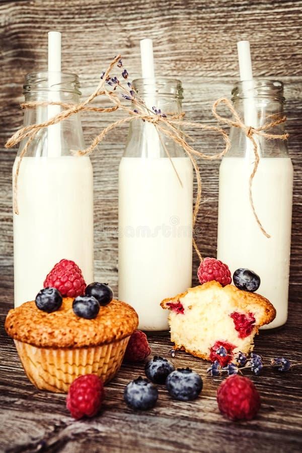 Melk in fles met Muffins met bosbessen en frambozen stock foto