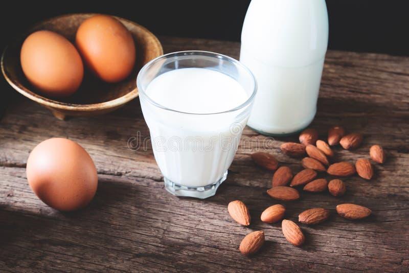 Melk in het drinken van glas en fles met eieren en amandelen royalty-vrije stock foto