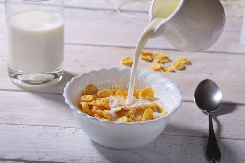 Melk het gieten in een kom heerlijke cornflakesgraangewassen en GLB met espresso Ochtendontbijt royalty-vrije stock fotografie