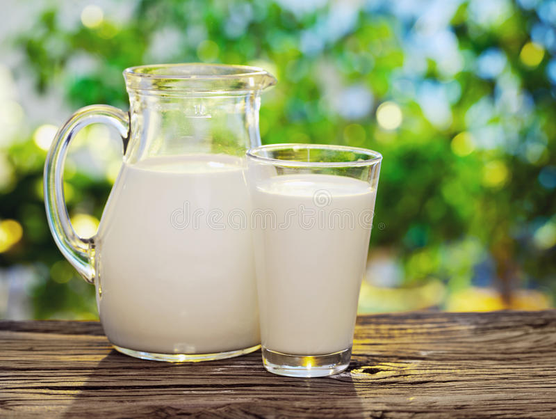 Melk in kruik en glas. stock fotografie