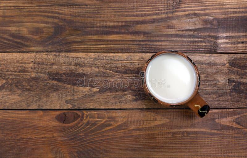 Melk in traditionele landelijke Mok op ruwe houten Lijst royalty-vrije stock afbeeldingen