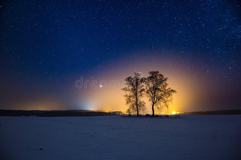 Melkachtige manier en sterrige hemel over de winterlandschap en ver dorp stock fotografie
