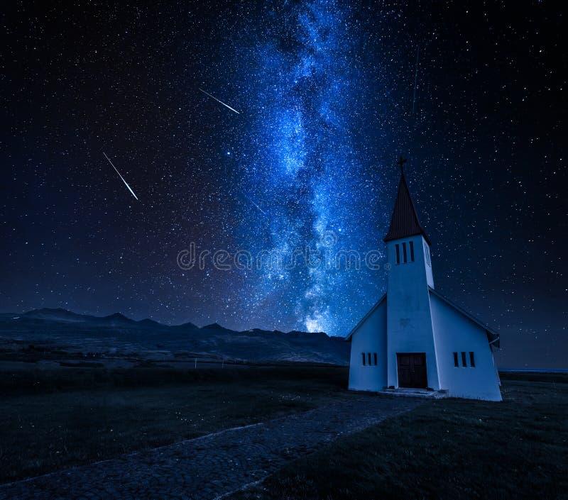 Melkachtige manier over kleine kerk in berg, IJsland in de zomer stock foto's