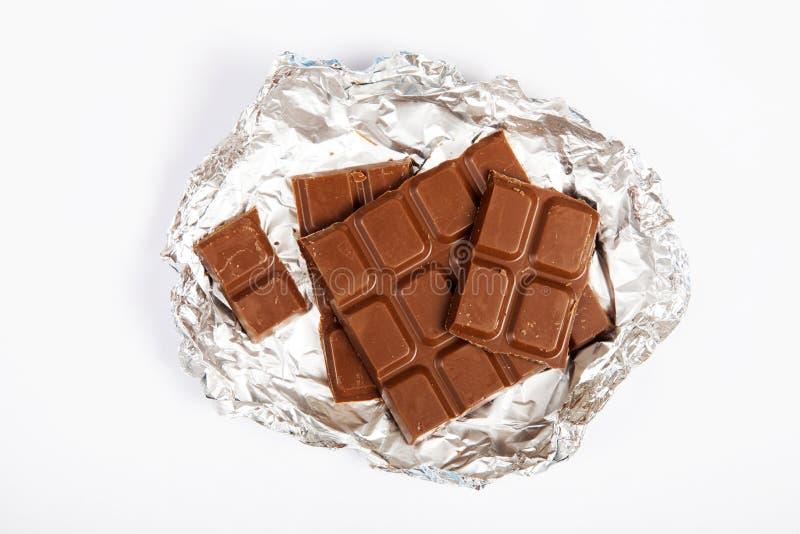 Melkchocolastukken op witte achtergrond van hoogste mening worden geïsoleerd die stock afbeelding