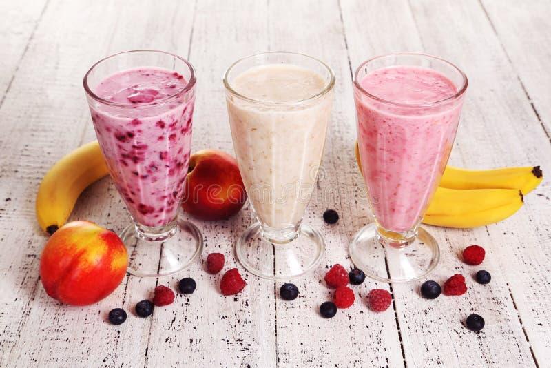 Melken Sie Cocktail mit Banane, schwarzer Johannisbeere und Himbeere in einem Glas auf weißem hölzernem Hintergrund stockfoto