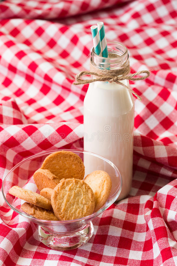 Melkfles en koekjes in een glaskom royalty-vrije stock afbeeldingen