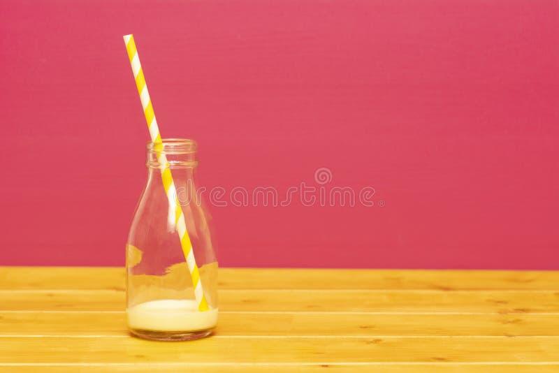Melkfles met residu's van banaanmilkshake en een stro stock foto