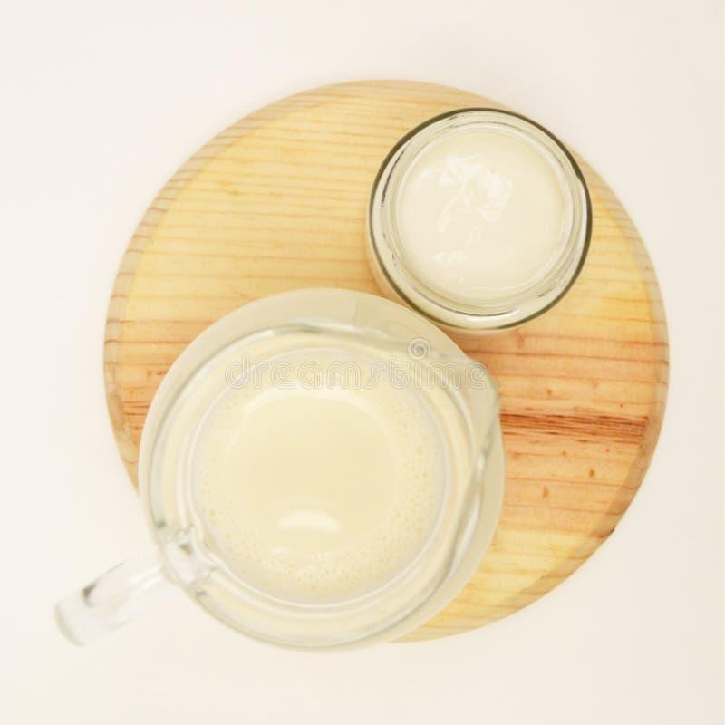 Melkkaraf en yoghurtkruik op houten raad en witte Hoogste mening als achtergrond stock afbeeldingen