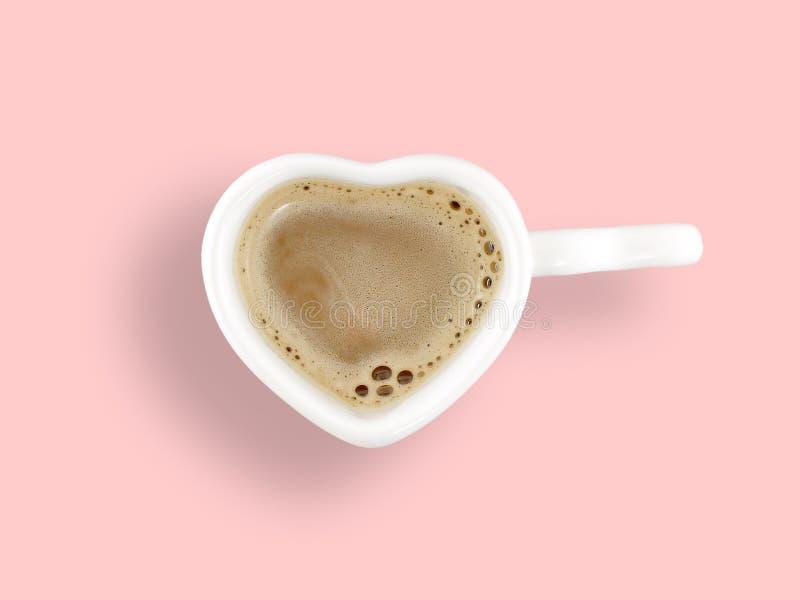 Melkkoffie in witte ceramische de koffiekop van de hartvorm op pastelkleur roze achtergrond royalty-vrije stock foto