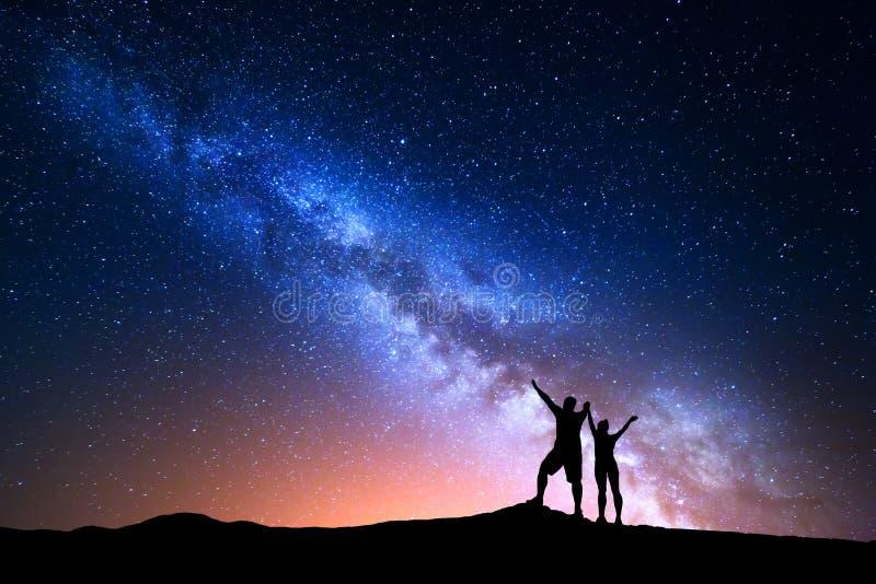 Melkweg en silhouet van gelukkige mensen royalty-vrije stock afbeelding