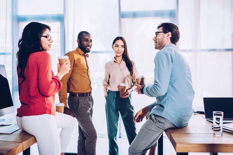 mellan skilda raser affärskollegor som har konversation under kaffeavbrott fotografering för bildbyråer