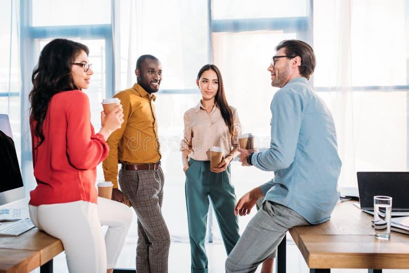 mellan skilda raser affärskollegor som har konversation under kaffeavbrott royaltyfri foto