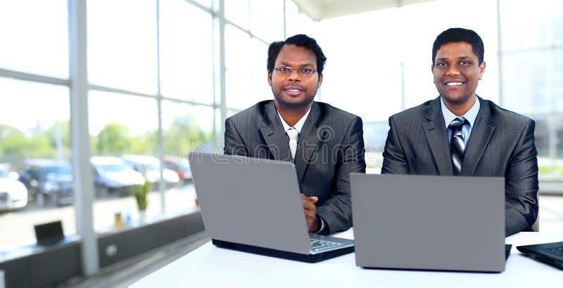 Mellan skilda raser affärslag som arbetar på bärbara datorn royaltyfria bilder