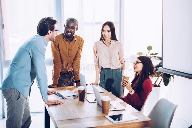 mellan skilda raser grupp av affärskollegor som diskuterar arbete under kaffeavbrott på arbetsplatsen royaltyfri bild